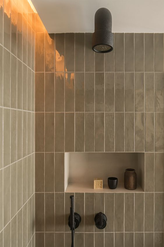 stacked taupe tiles in shower with black fixtures and statement niche