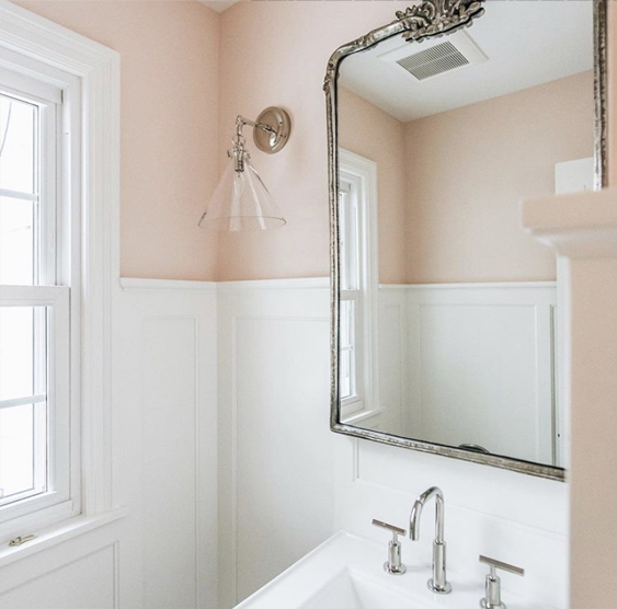 blush painted bathroom with chair moulding and silver sconce
