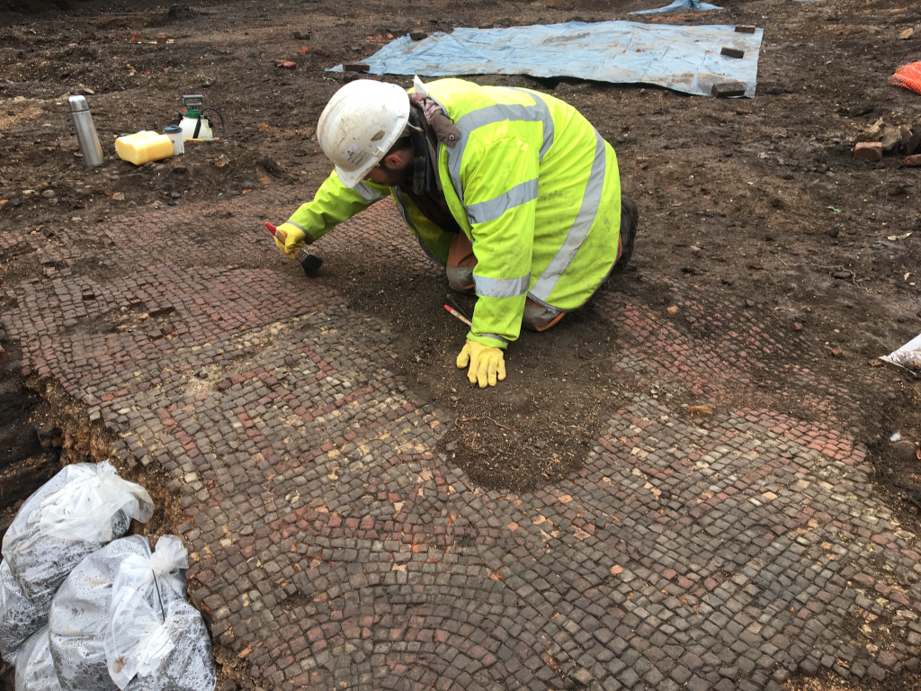 Archaeologist Richard Huxley carefully cleans the mosaic pavement. Credit: Mathew Morris/ University of Leicester