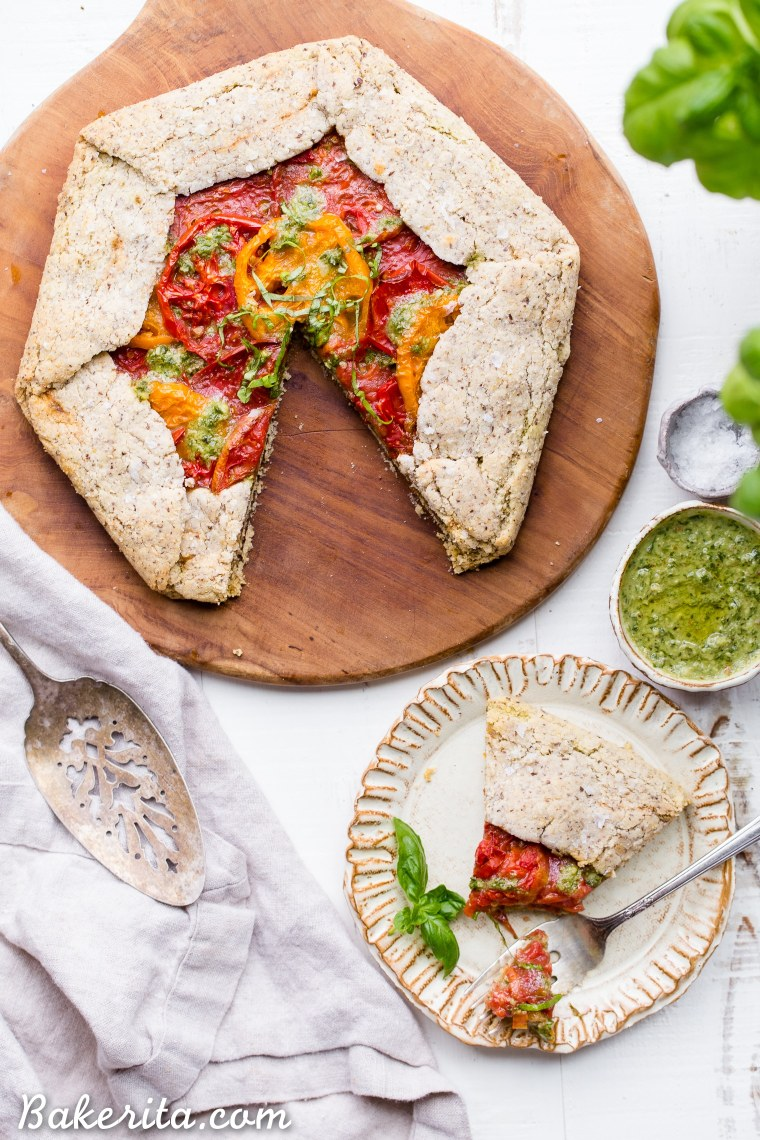 This Pesto + Heirloom Tomato Galette has an incredibly flaky, savory crust filled with homemade pesto and thick slices of heirloom tomatoes. Served warm, it's a truly delicious appetizer or meal that you'd never guess is gluten-free, paleo, and vegan.
