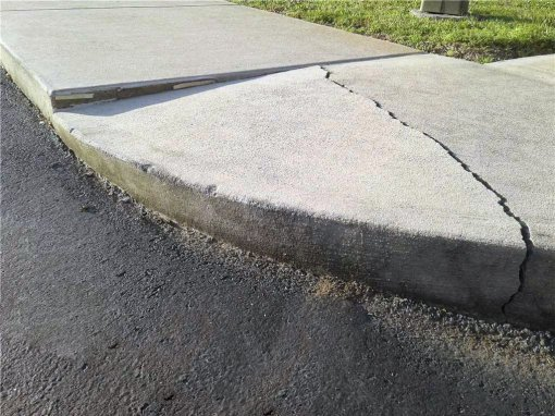 Concrete sidewalk cracked and sunk in.