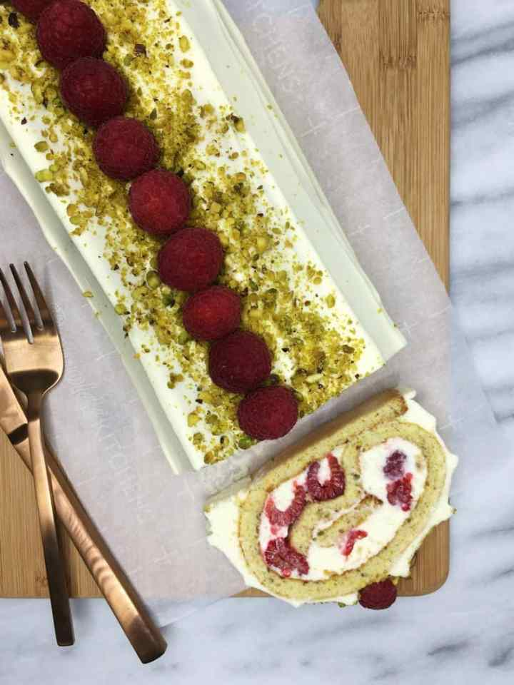 Raspberry Pistachio Roulade on a wooden cutting board with a fork and a knife: Bird View