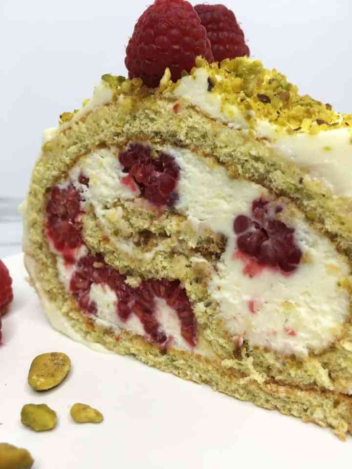A thick slice of Raspberry Pistachio Roulade on a white plate: Close up