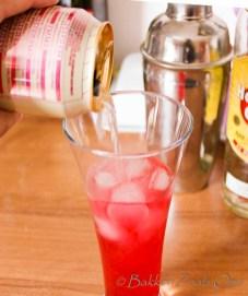 Glas met cherry whispers cocktail mix wordt aangelengd met gemberbier