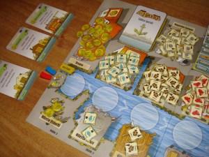 """In alto le sei carte edificio speciale, alcuni magazzini, e sotto l'inizio della """"corsia dei turni"""", divisa in sette spazi. In basso le merci grezze a disposizione dei giocatori."""