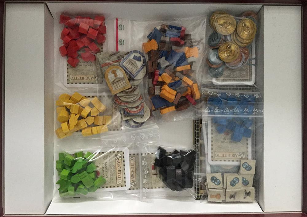 Oltre alla plancia oversize, all'interno della scatola troviamo tante bustine con segnalini di legno colorati e un bel quantitativo di carte.