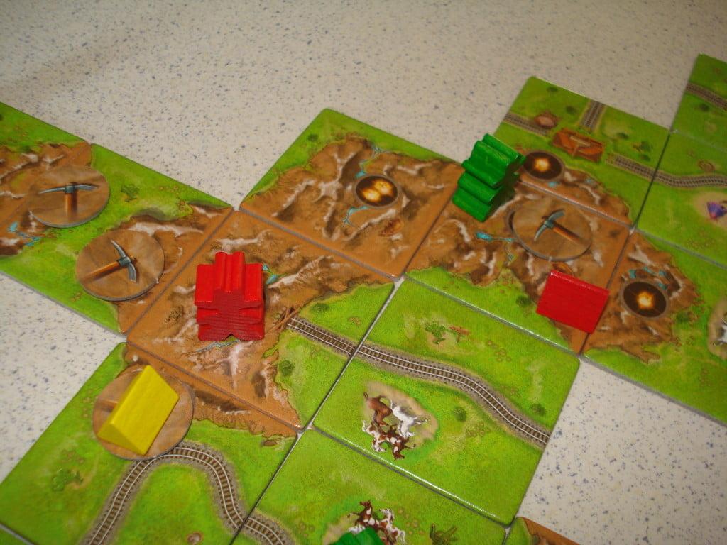 Si possono creare situazioni come quella in figura: tende e meeple multipli sulla stessa montagna! Finita la montagna i giocatori rosso e verde si spartiscono le pepite, e guadagnano entrambi il bonus di completamento.