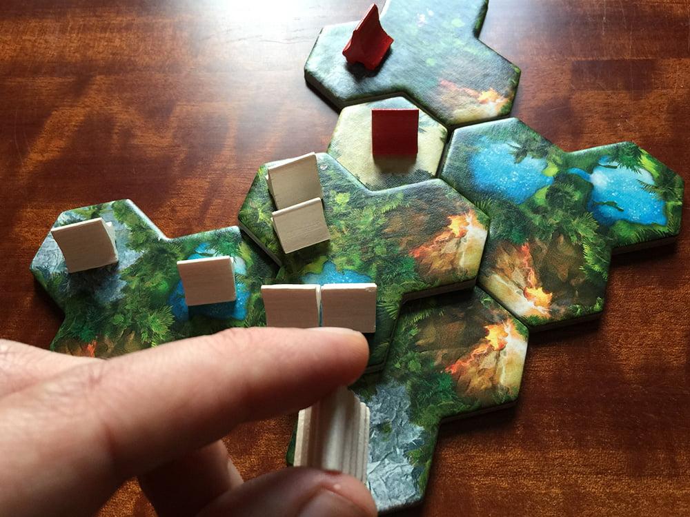 Il giocatore di colore bianco sta ampliando il suo villaggio: al centro potete vedere che ha costruito due capanne in un esagono di secondo livello, mentre in basso sta per sorgere il tempio.
