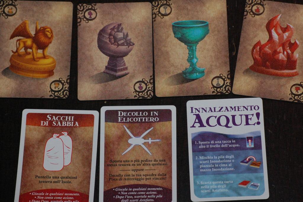 Carte Artefatto. In alto gli indizi per recuperare gli artefatti, in basso le altre carte.