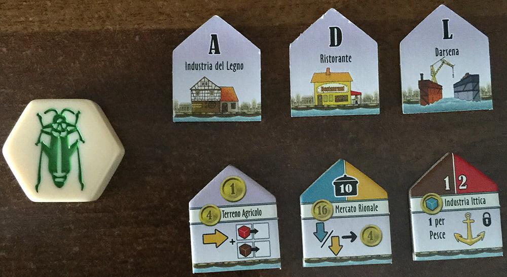 6 dei 31 edifici inclusi (in alto si vede il retro, in basso il fronte). Inseriamo una pedina di Hive Pocket per aiutarvi a comprendere le dimensioni di ciascuna tessera.