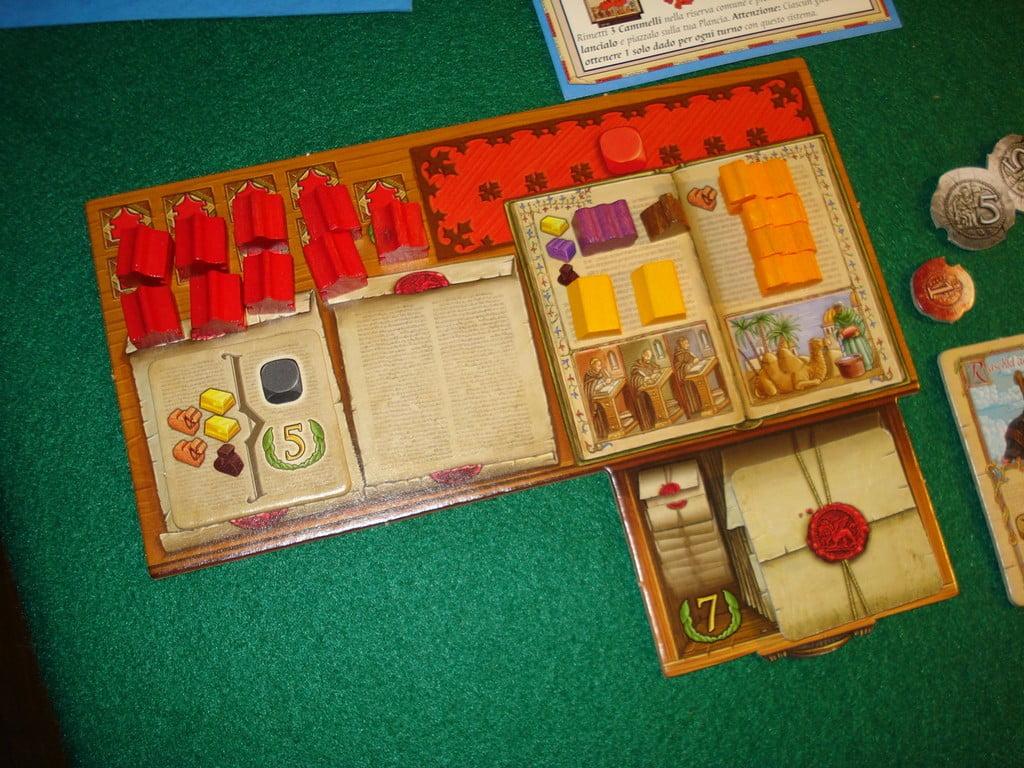 Plancia del giocatore rosso, con a sinistra gli avamposti commerciali ancora da piazzare, e sotto lo spazio per i due contratti attivi; a destra spazio per dadi (in alto), merci, cammelli e in basso i contratti completati.