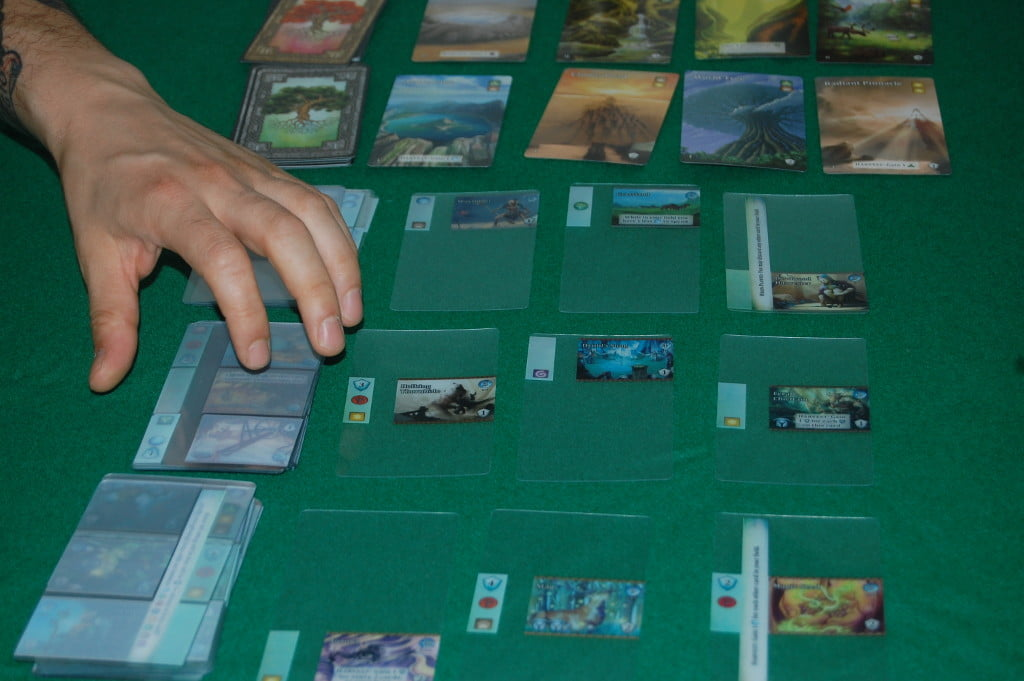 Il setup: in alto le carte obiettivo che presto saranno oggetto dei nostri acquisti, tre livelli di carte potenziamento trasparenti e un ulteriori mazzo di carte trasparenti. Ogni giocatore riceve un mazzo di 20 carte uguali per tutti.