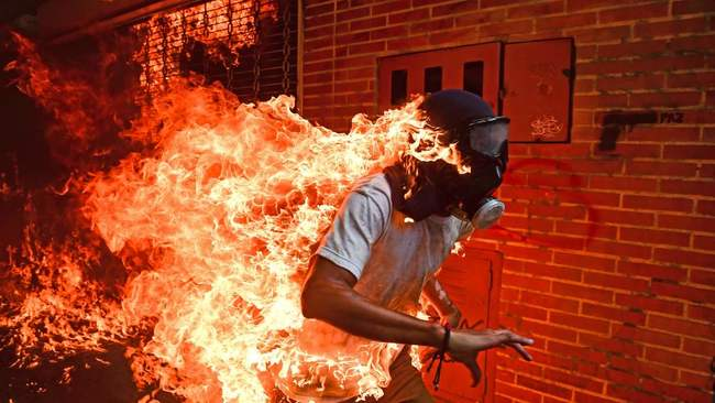 (FILES) This file photo taken on May 3, 2017 of a demonstrator catching fire during clashes with riot police within a protest against Venezuelan President Nicolas Maduro in Caracas, by AFP Venezuelan photographer Ronaldo Schemidt won the World Press Photo (WPP) picture of the Year 2018 award and 1st prize in the Spot News Singles category in Amsterdam on April 12, 2018. / AFP PHOTO / RONALDO SCHEMIDT