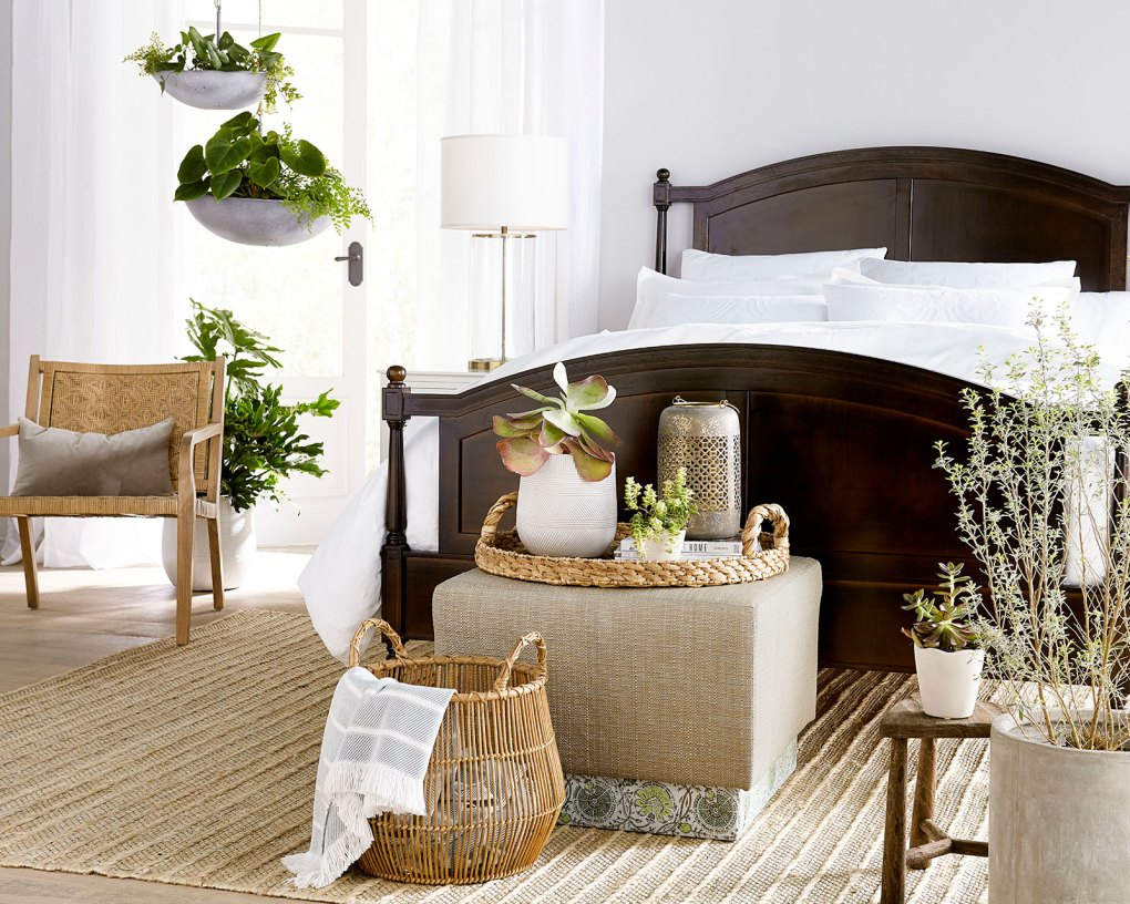 Vacation-inspired bedroom with white bedding, dark brown bed, and woven textures