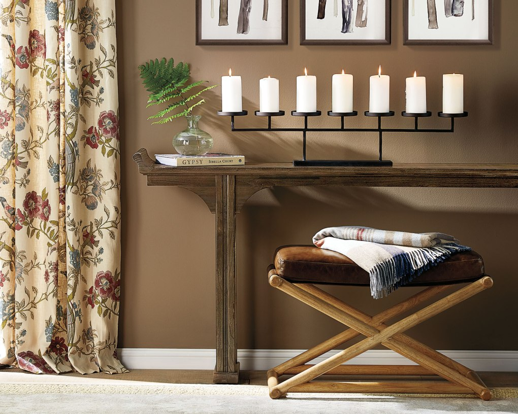A leather furniture bench sitting underneath a wood console table