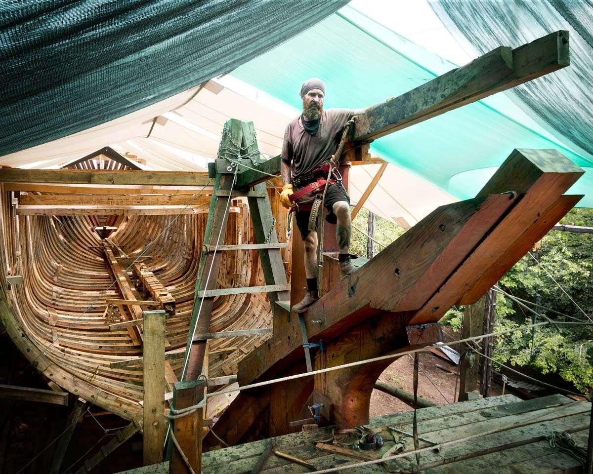 A WOODEN CARGO SHIP, STEAMING HOT UNDER A TROPICAL SUN