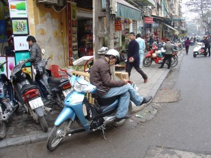 A man sitting on his motorbike waiting for customers