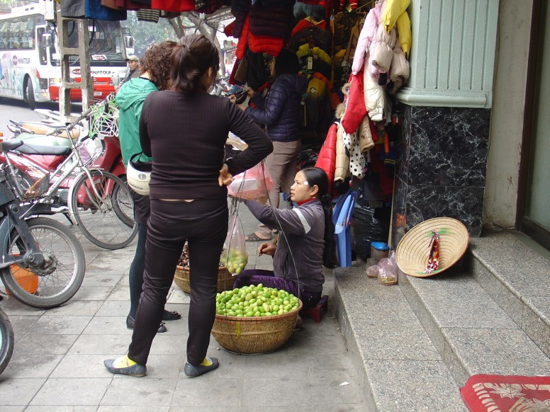 A vendor selling green fruits