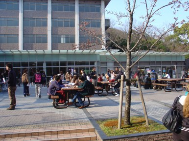 Students resting on benches in front the cafeteria.