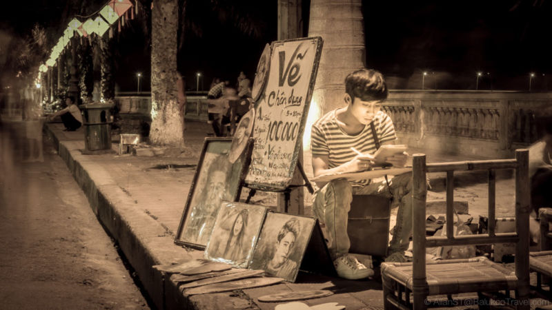 Engrossed artist at Hue Walking Street (Night Market). Hue, Central Vietnam.