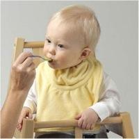 Koo-di Snugease Bib yellow on a baby in a highchair