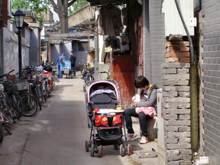 Mutter mit Kind und Kinderwagen im Hutong