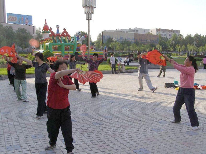 Frühmorgens auf einem Platz im Zentrum von Yili, Provinz Xinjiang, Fächer Qigong