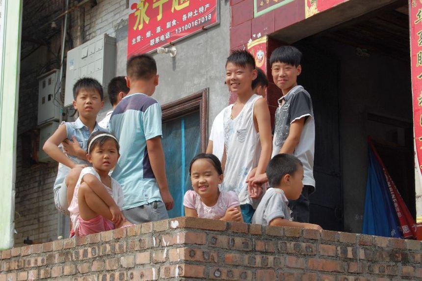 2015 Fröhliche Kinder, die genau beobachten, was die westlichen Besucher so machen