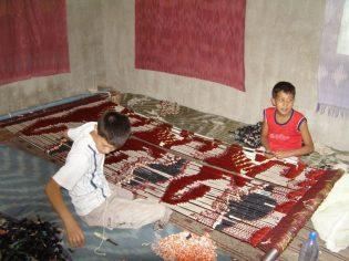 Jungs beim Färben der Seidenstoffe