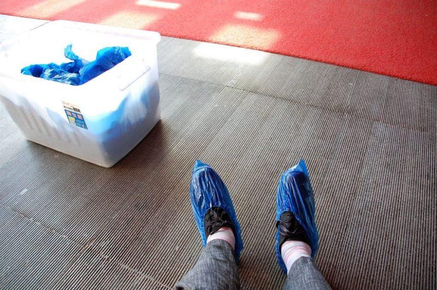 Han Yang Ling ich ziehe Plastikschutz über meine Schuhe.