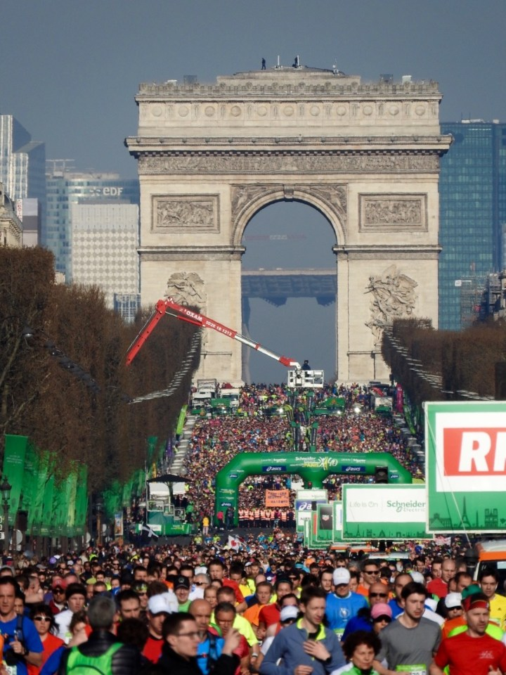 Paris Marathon start on the Champs-Élysées with 1000s of runners and the Arc de Triomphe in the background