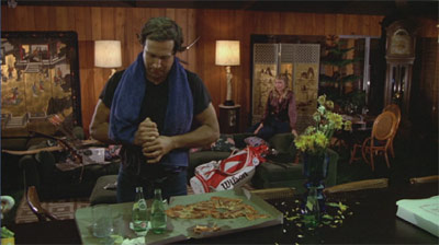 """Ty Webb's home is a marvel of subtle set design. Aside from the pile of uncashed checks, note the stake pizza and Perrier, the random sporting equipment, the wood paneling, the wilted flowers, and the """"Benihana"""" decor, which Chase spontaneously damages when welcoming in his date."""