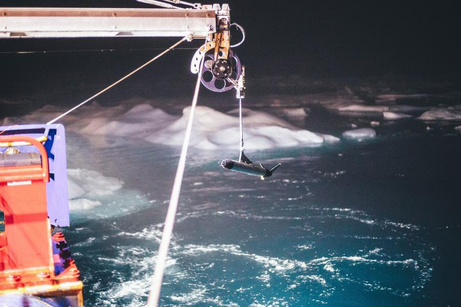 A piece iof equipment hangs from the side of a ship above an icy sea