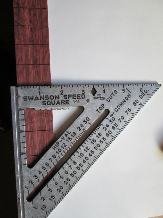 A carpenter's square is used to assist in cutting fret slots.