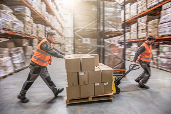 Return to Work program, two men moving boxes in a warehouse