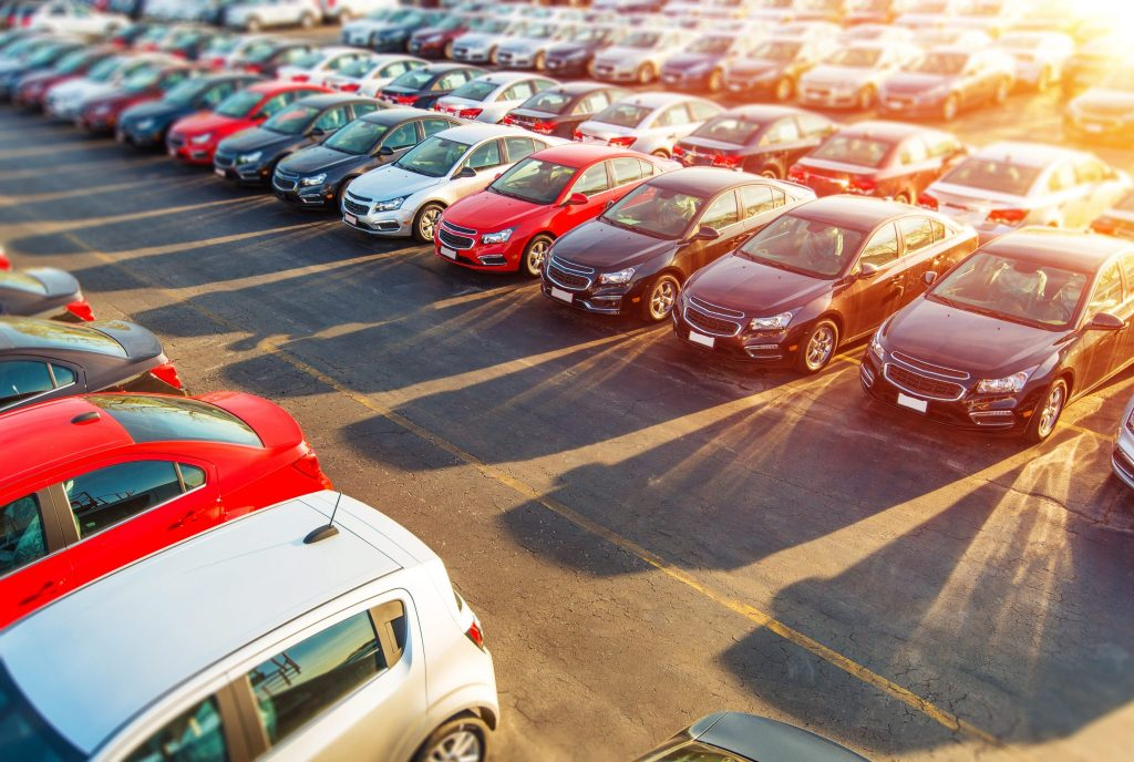 Garage insurance auto dealers open lot insurance. Rows of colorful vehicles in a dealer lot.