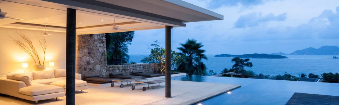 High value home insurance, villa patio scene next to infinity pool at dusk overlooking blue sea with islands in background.