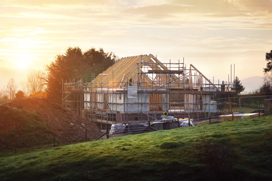 Framing contractor general liability insurance, mountain home under construction showing bare roof trusses and scaffolding with sunset in background.