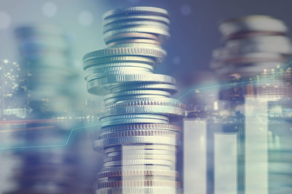 Financial institutions insurance liability, a stack of coins overlaid with a cityscape and graph.