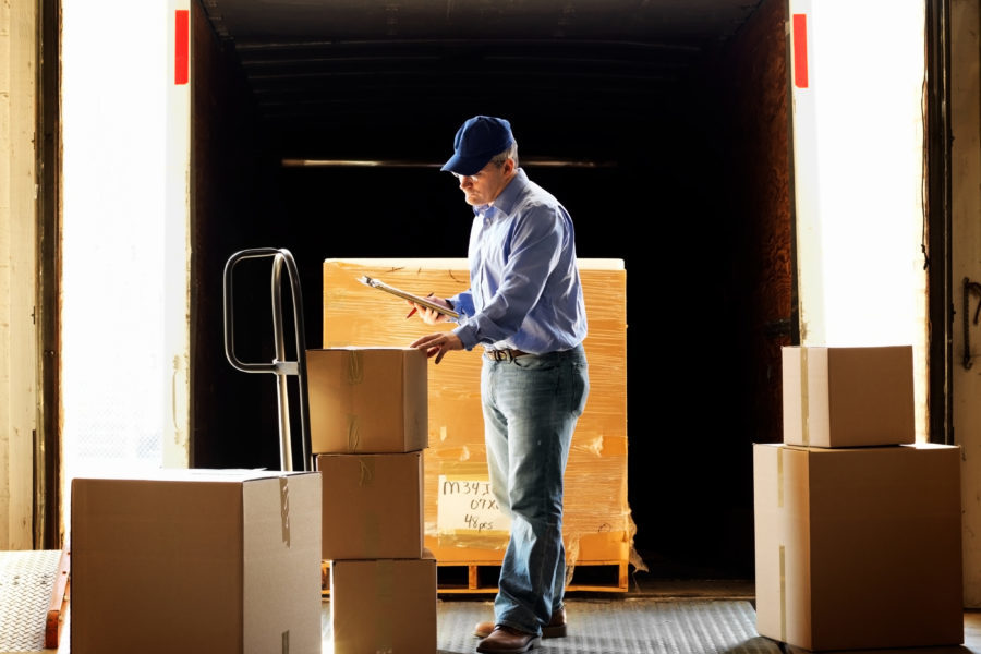Semi truck insurance general liability, truck driver standing on loading dock, inspecting boxes.