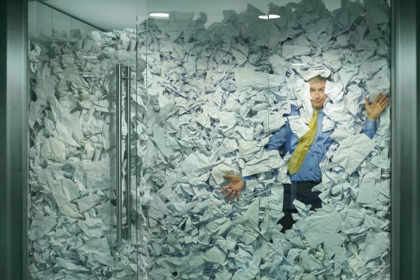 Paper or PDF, businessman smashed against glass wall by paper. Paperless office.