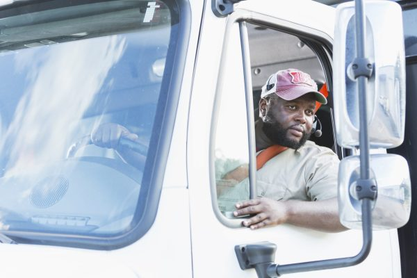 Truck driver recruiting and retention, commercial driver looks in side view mirrors while backing truck.