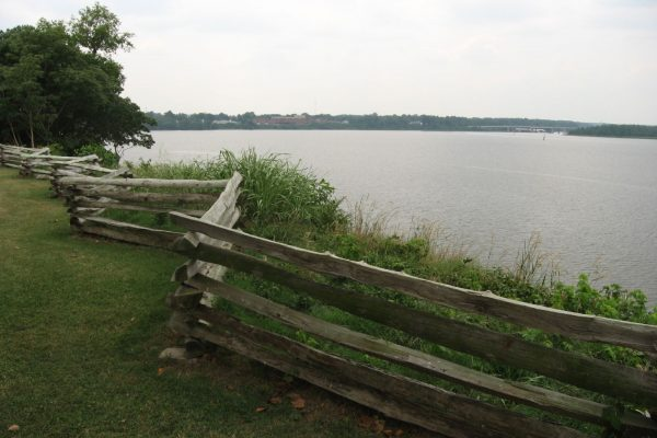Sutherland, VA City Point, view of river from overlook of green lawn with split rail fence in foreground.
