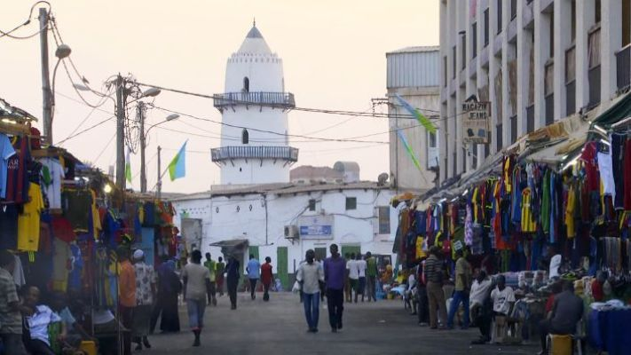 People, street vendors, a white building, clothes
