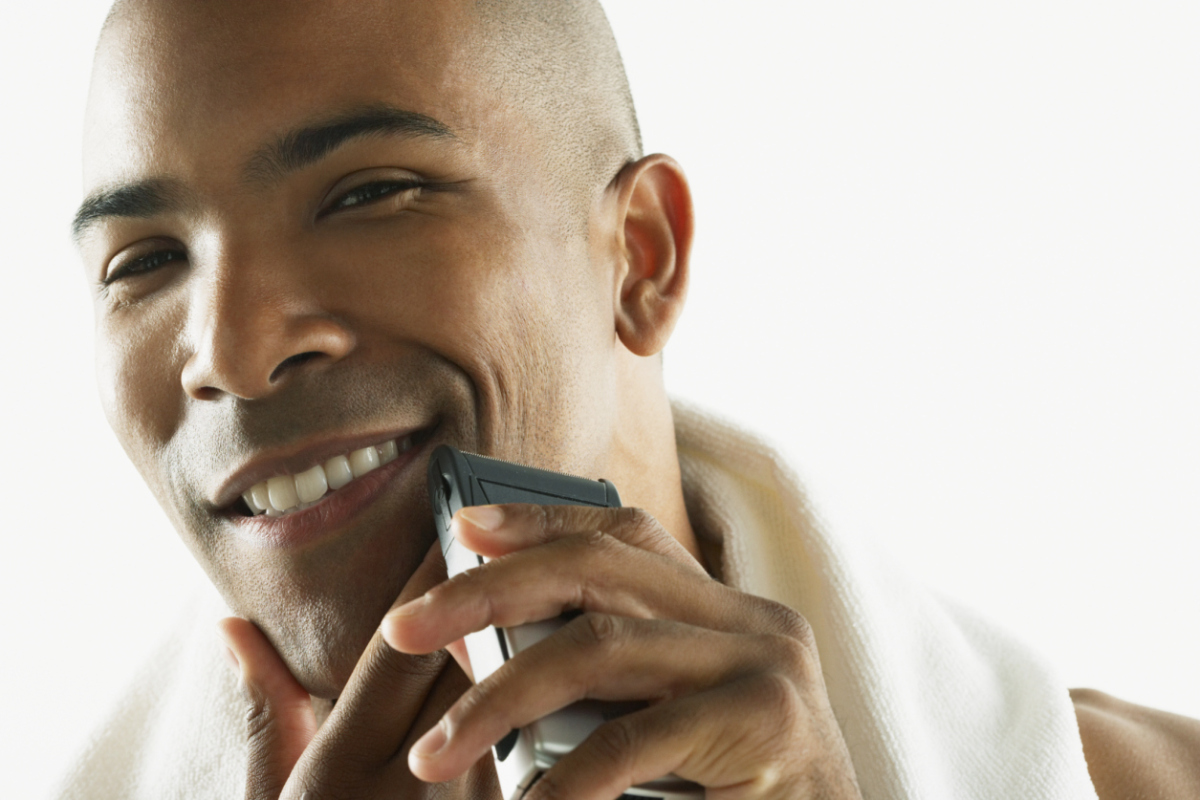African American man shaving face with electric razor