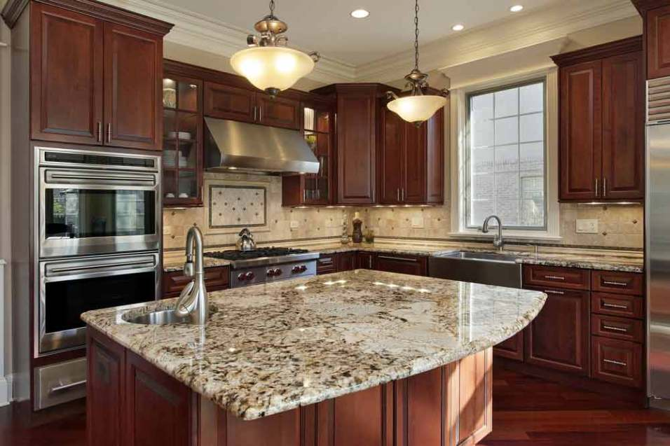 A warm kitchen space with a granite slab countertop.