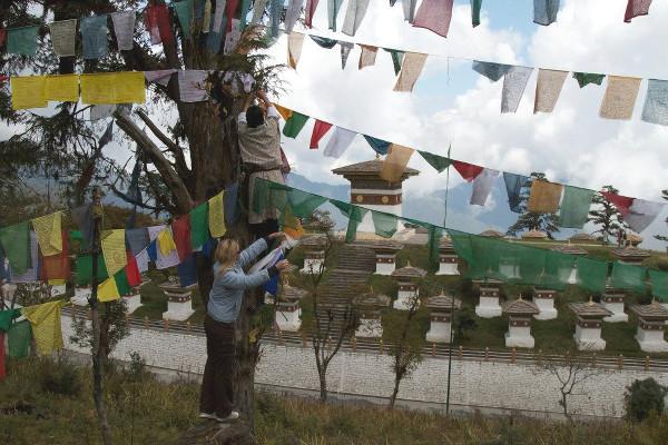 Claire accroche des drapeaux de prières dans un arbre