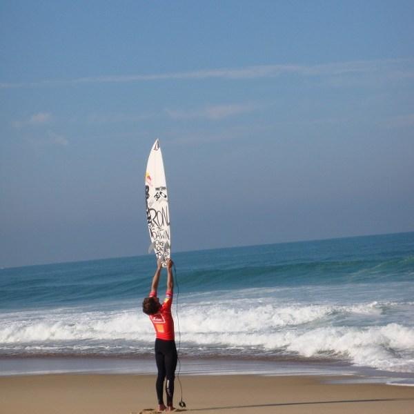 Un surfeur s'étire sur la plage à Hossegor