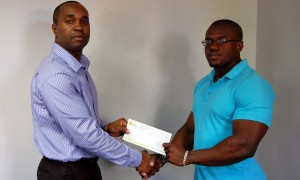 Terry Yearwood presents Mr. Barbados, Ramon Broomes, with his sponsorship cheque.