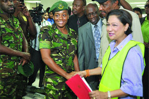 Prime Minister Kamla Persad-Bissessar (right) greets Private Spencer (centre) of the Trinidad and Tobago Defence Force during her tour of the Inter-Agency Task Force yesterday. Looking on are National Security Minister Jack Warner (third from right) and Senior Superintendent Carlton Alleyne (second from right).